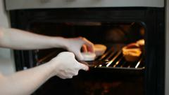 The girl puts muffins in an oven Stock Footage