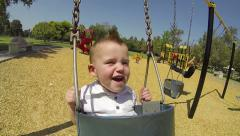 Cute Baby Boy On Swing At Park In Summer Stock Footage
