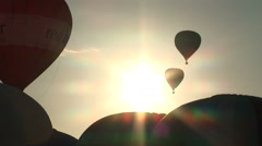 Hot air balloons rise against morning sun Stock Footage