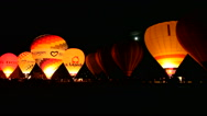 Stock Video Footage of A row of Hot Air Balloons light up the night