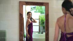 Beautiful woman looking at her appearance in the mirror HD Stock Footage
