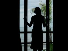 Woman unveil curtains, walking out on terrace with view at sea NTSC Stock Footage