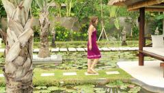 Woman walk, sit and relax in beautiful gazebo bed in garden HD Arkistovideo