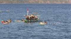 Group of fishermen hauling in large fishing net onto their boat Stock Footage