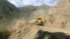 Front end loader and diggers move rocks and earth to widen main road Stock Footage