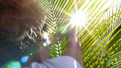 Female Reach out for Sunlight through Leaves of Palm Tree. Stock Footage
