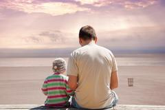 Father and daughter on empty beach at sunset. Stock Photos
