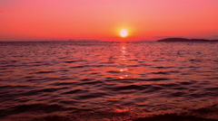 Sunset on sea coast. Clean evening sky and ocean water ripples with light of sun - stock footage