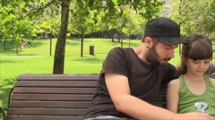 Very Young Father With His Daughter In Park Using Tablet PC, Outdoors, Pan Stock Footage