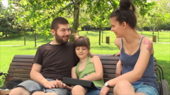 Very Young Parents, With Daughter Playing On A Tablet PC, Front Shot, Outdoors Stock Footage