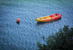 moored yellow red plastic lifeboat - stock photo