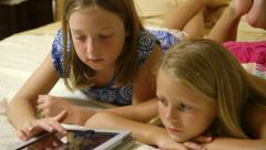 tilt to little girls playing games on tablet pc - stock footage