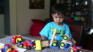 Stock Video Footage of Little Asian Boy Plays With His Toys After Colouring