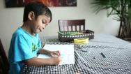 Stock Video Footage of Cute Asian Boy Spends Time Colouring Pictures