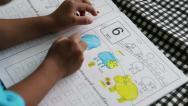 Stock Video Footage of Asian Boy Spending Time Doing School Workbook