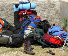 backpacks bags and boots piled up after the long walk of the boyscout  - stock photo