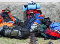 backpacks and boots piled up after the walk of the boyscout  - stock photo