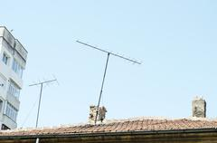 orange roof tiles, chimney and old analog tv antenna - stock photo