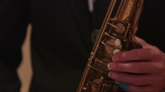 Close up of a man's hands and mouth playing saxophone, tuxedo Stock Footage