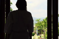 Woman looking out the window at garden, super slow motion, 240fps NTSC Arkistovideo