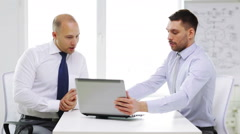 Two serious businessmen with laptop in office Arkistovideo