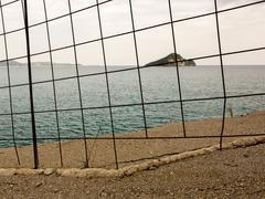 Stock Photo of Distant island behind a iron fence