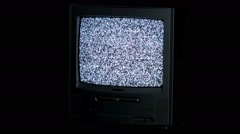 Small analog tv with no signal noise in dark room Stock Footage