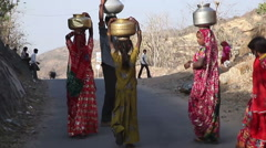 Indian village girl carry jugs of water Stock Footage