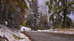 Bicyclist riding on the road. Uphill. First snow Stock Footage