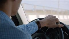 Young driver turns the steering wheel driving fast on a highway - stock footage