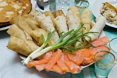 Pancakes with salmon slices and green onion (russian cuisine dish) Stock Photos