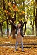 happy little girl playing with autumn foliage in a park - stock photo