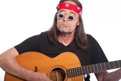 Middle-aged bohemian male artist playing guitar Stock Photos