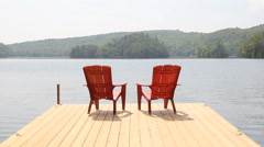 Two red chairs on cottage dock. Sunny morning. Medium shot. Stock Footage