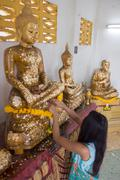 girl sticks a slice of golden on Buddha statue - stock photo