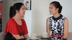 Two Asian Women Sharing Time Together In Cafe - stock footage