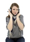 Beautiful young smiling woman listens to music with headphones on her head Stock Photos