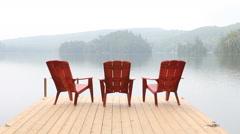 Three red chairs on dock. Misty morning. Stock Footage