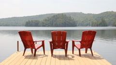 Three red chairs on dock. Sunny morning. Stock Footage