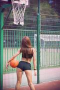 beautiful young woman with fluttering hair playing basketball outdoors - stock photo