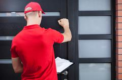 Delivery man knocking on the client's door Kuvituskuvat