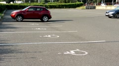 Parking spaces in the parking lot for the disabled - busy urban street with pass Stock Footage