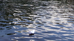Small origami paper ship float on ripple river water. Follow Stock Footage