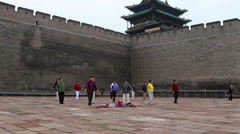 People doing morning exercises under Pingyao ancient city wall Stock Footage