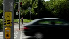 Pedestrians waiting at traffic lights - busy urban street with cars: nature Stock Footage
