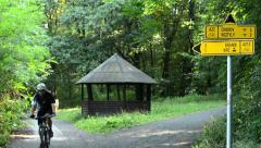 Path labels in the forest (park) - cyclist passes - trees with wooden shelter Stock Footage