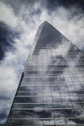 Business, skyscraper with glass facade and clouds reflected in windows Stock Photos