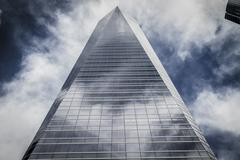 Skyscraper with glass facade and clouds reflected in windows Stock Photos