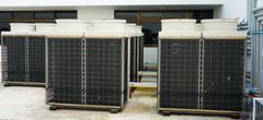 row of air conditioning units on rooftop - stock photo