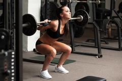 Beautiful girl exercising squatting with barbell - stock photo